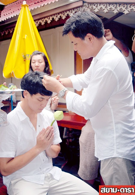 khun Boy snipping a few strands off his hair...
